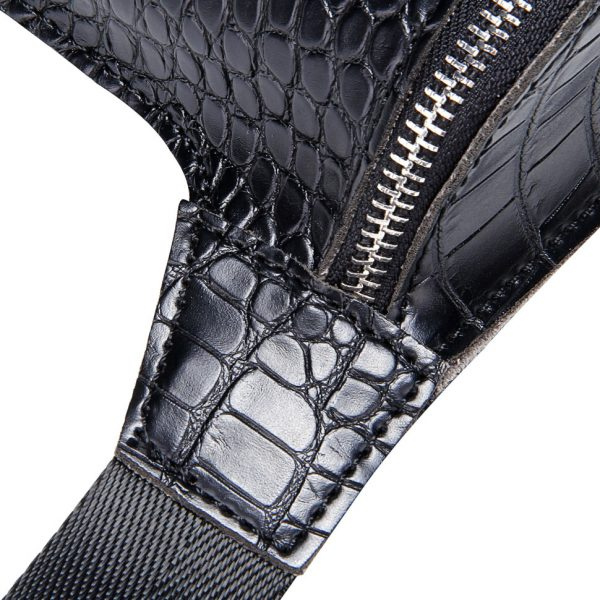 A photo showing the connection of the black waist bag with an alligator pattern. It's a closeup of how the bag is stitched together with the belt.