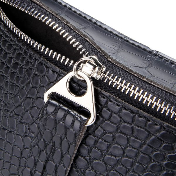This photo shows the closeup detail of the zipper and the handle of the black waist bag with an alligator-patterned leather.