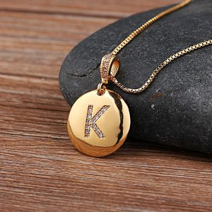 "A photo showing a close up of the pendant with the letter ""K"" as an initial on a gold necklace."