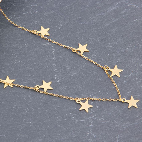 Star Gold Necklace laid on a stone surface close up photo
